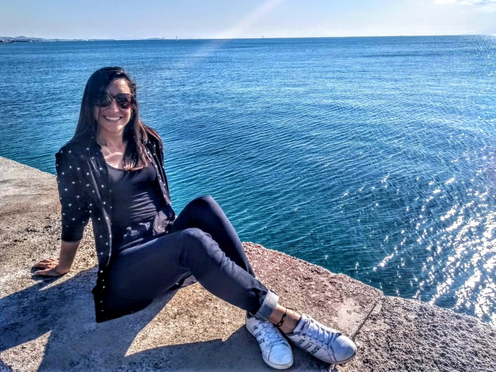 Carolina sentada a lado del mar Mediterráneo en Flisvos Marina , Athenas.  Esta no es una foto en bikini! Es una representación de su cambio de vida.  Su sonrisa y expresión relajada son muestra de su satisfacción por dedicar su vida a ayudar a las personas a vivir vidas más saludables.
