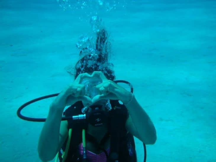 Caro underwater, hands making the shape of a heart